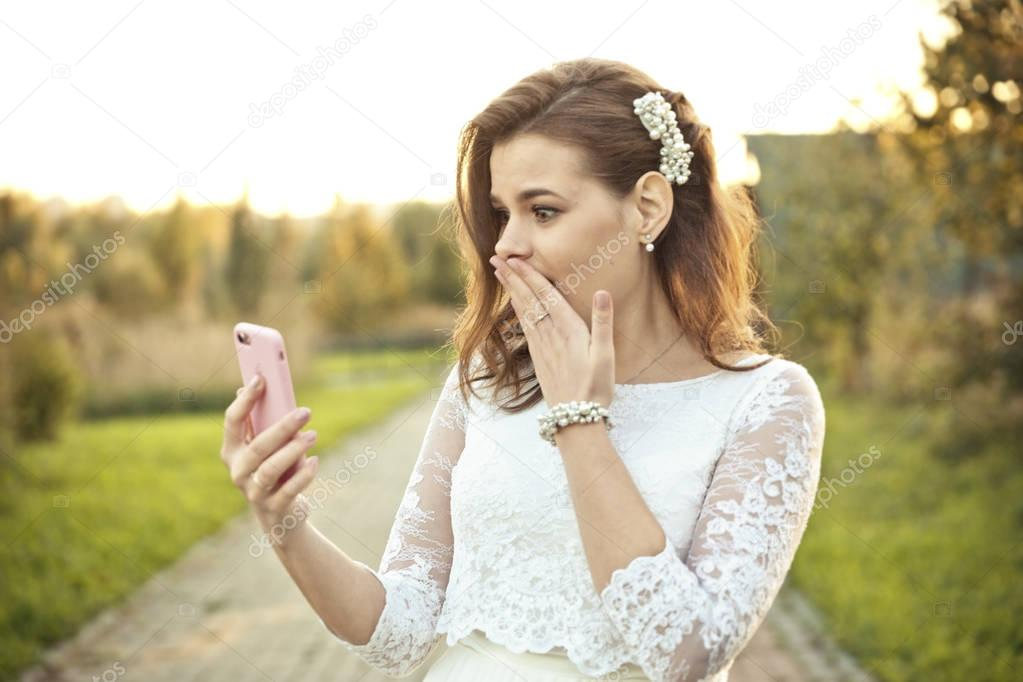 Shocked girl in wedding dress looking at mobile phone in pink cover