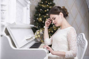 Young bride in white wedding dress playing piano Christmas tree background
