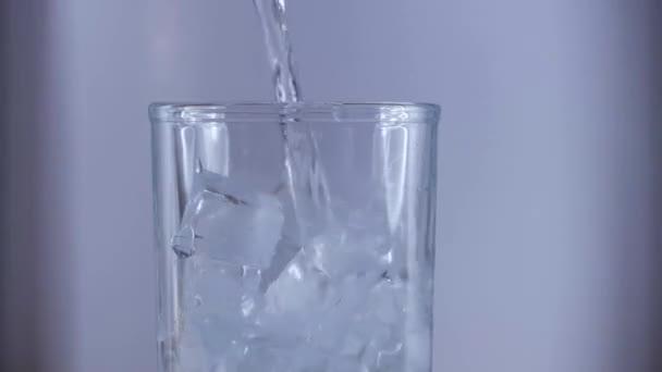 Čistá pitná voda s ledem ve sklenici.
