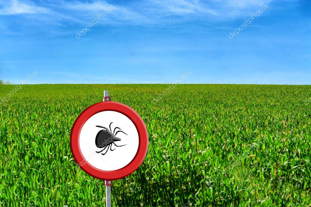 Green field and tick warning sign