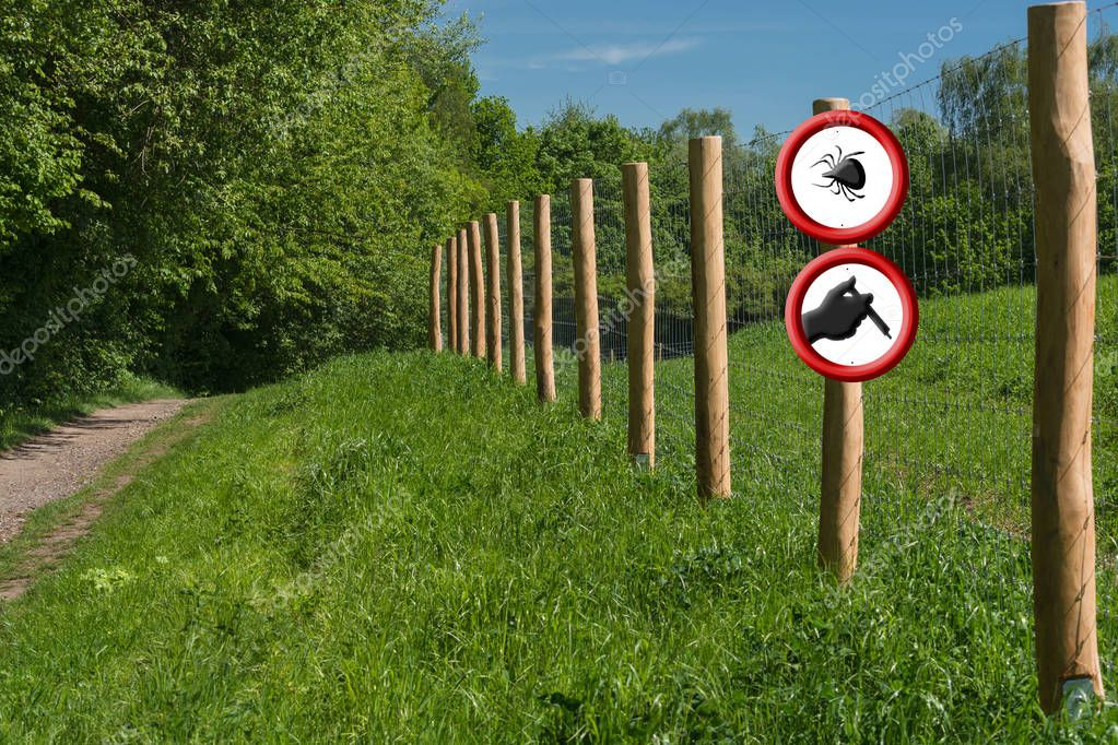 Two round red warning signs on a fence post in front of a green