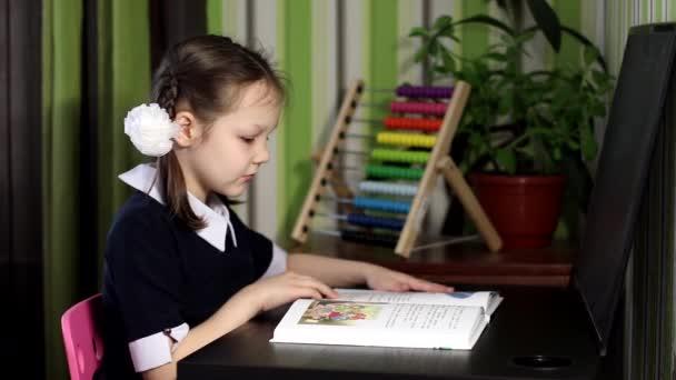 Online-Fernunterricht. Ein Mädchen blättert in einem Buch, betrachtet Bilder in einem Buch, eine Schülerin studiert zu Hause am Tisch.