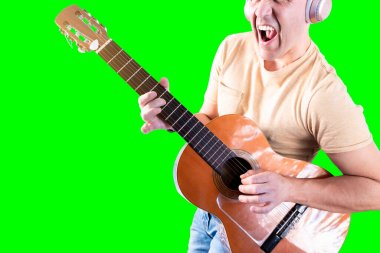 excited man sings and plays guitar like a famous rock singer in his bedroom.