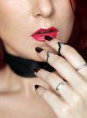 Žena ruku s kroužky dotýká zářivě červené rty