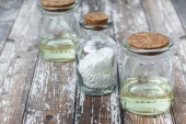 Classical Homeopathy globules  and vintage glass bottles on wooden background. Alternative Homeopathy medicine herbs, healtcare and pills concept.   Place for text.