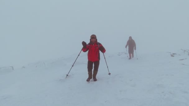 Two men with trekking sticks climb a mountain in the fog.