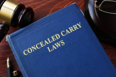 Concealed Carry Laws title on a book and gavel.