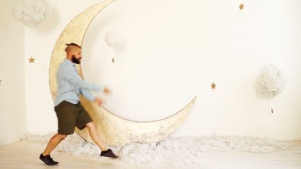 Férfi tánc közelében dekorációk, a Hold és a felhők. Őrült álmok koncepció.