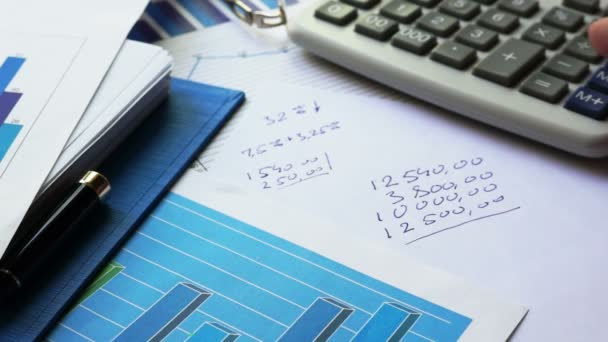 Man calculating profit using calculator and writing financial figures.