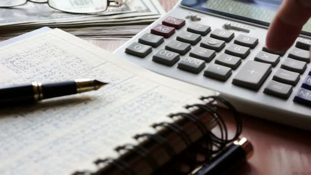 Accountant using calculator for checking financial report. Table with papers and money.