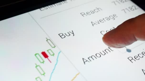 Detailní záběr z obrazovky telefonu s burze obchodování data.