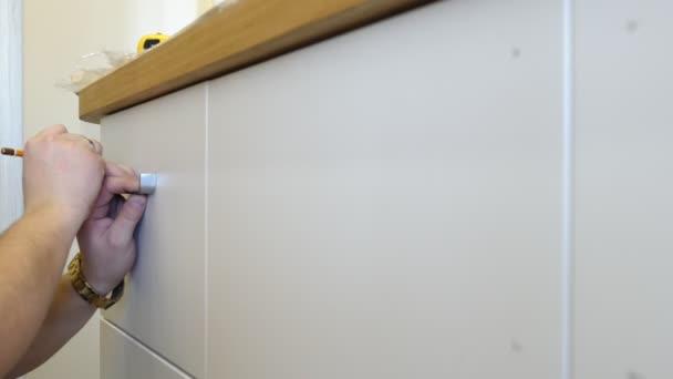 Tischler, Vorbereiten der Installation Griffe auf einem Schrank. Möbel Montage.
