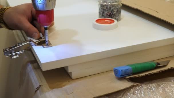 Hand mit Schraubendreher für die Montage von Möbeln. Weißer Schrank installieren.