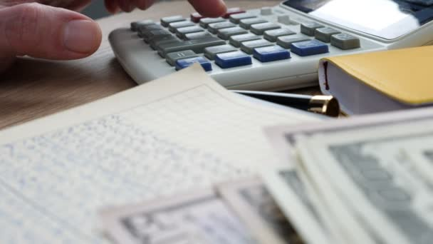 Businessman using calculator and accounting book for financial calculations.