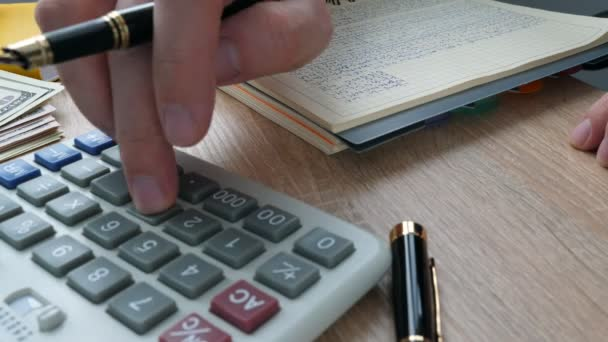 Businessman using calculator for checking financial results in an accounting book.