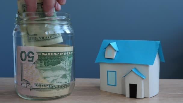 Peníze za dům. Rukou dát dolarové bankovky v jar a model domova.