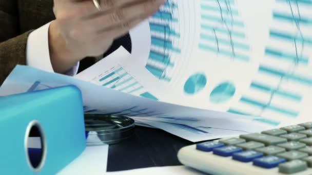 Accountant or auditor checks financial statements and charts. Paperwork in the office.