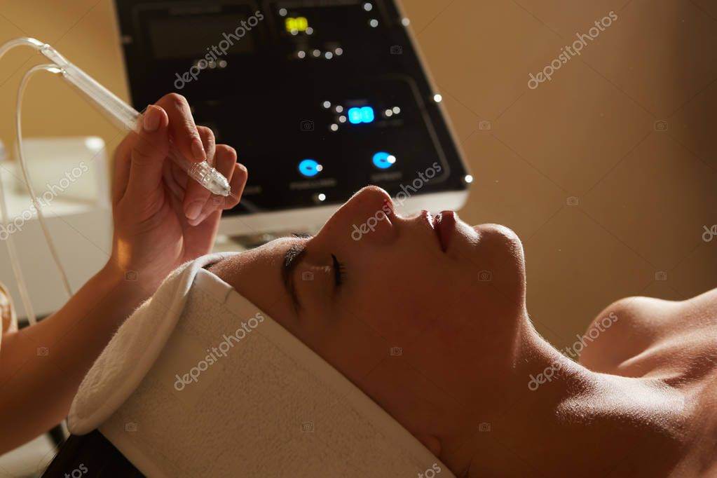 Face Beauty Treatment. Closeup Of Beautiful Woman Getting Facial Gas-liquid Oxygen Water Epidermal Peeling Using Professional Equipment At Cosmetology Center. Skin Care Concept.