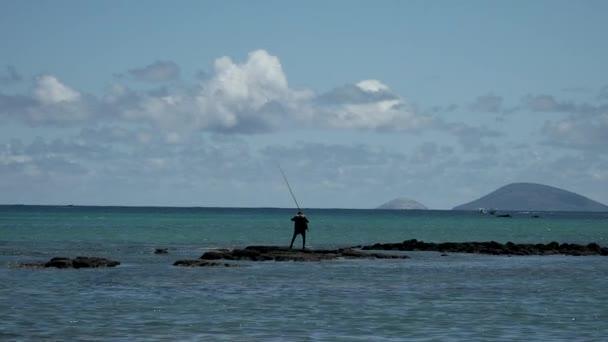 Halászok, akik sziklán állnak az óceánban, és halakat horgásznak.