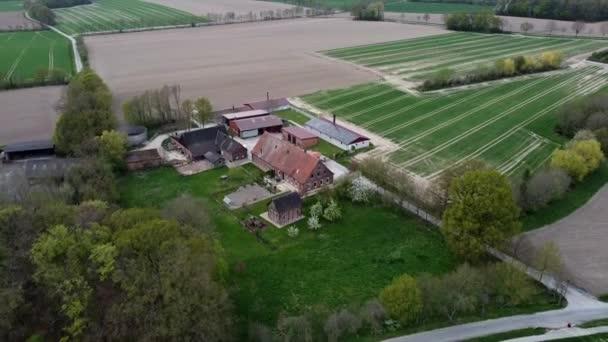 Luftflug über Bauernhaus, umgeben von landwirtschaftlichen Feldern