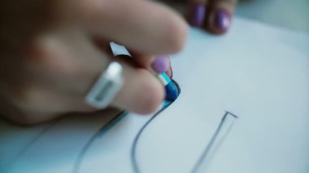 close up view of woman s hand coloring layout of shoes with blue pencil young designer developing new collection