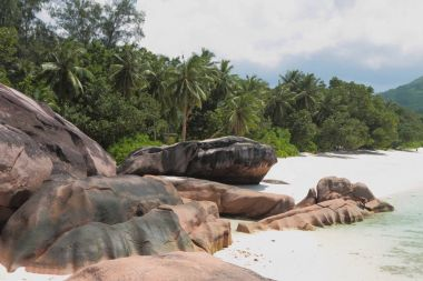 Basalt boulders on sandy beach. Baie Lazare, Mahe, Seychelles