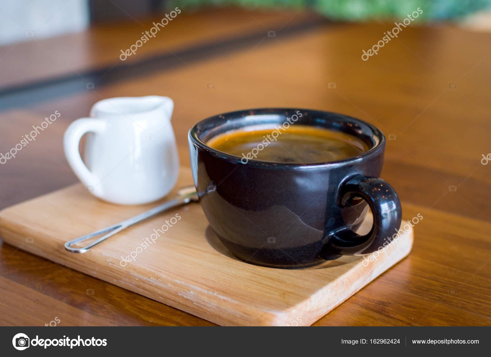 dunkel schwarz blau kaffeetasse mit kaffee americano l ffel und ein milchk nnchen auf einem. Black Bedroom Furniture Sets. Home Design Ideas