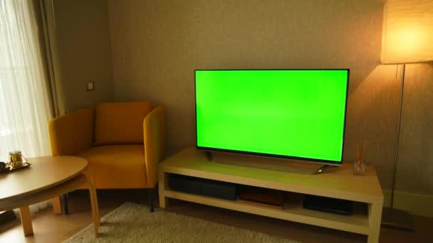 8k 76804320 30p. Připraveno nahradit zelenou obrazovku libovolným záběrem nebo obrázkem, který chcete. Můžete to udělat s klíčovým efektem klávesy chroma v libovolném softwaru pro editaci videa. Obývací pokoj pro odpočinek v domě. Televizní monitor s plochou obrazovkou doma. Zobrazit CD