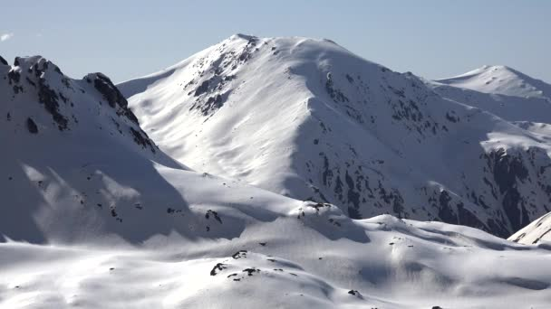 Time-lapse shadows covering the snowy hillside. Shadows grow as time progresses. Deep snowy valleys. Continental polar climate. Mountain chain. Vertical slopes. Broken steep cinematic best sky nature.