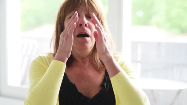 Mature woman with allergy sneezing and blowing her nose