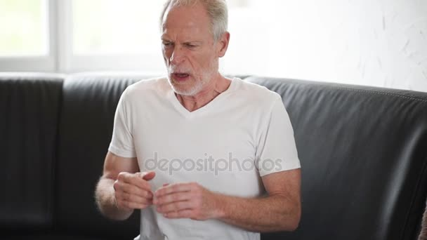 Starší muž s alergií, kýchání a smrkání jeho