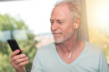 Portrait of mature man listening music with earphones, light eff