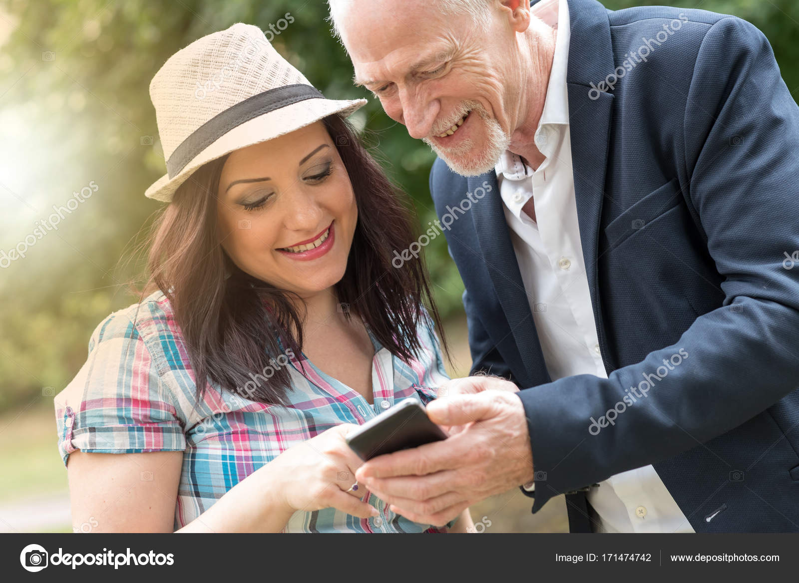 Happy young woman and mature man using a mobile phone, light ...
