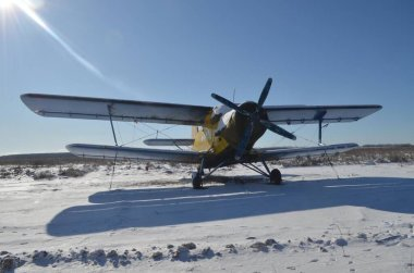 An AN-2 airplane was parked in the winter time. It is frosty, cold, sunny day, we see snow on the street. The airplane is wrapped and moored.