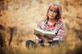 Nő olvasókönyv a parkban a fűben