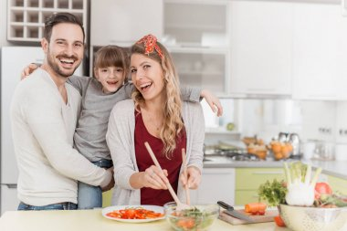 Happy family in the kitchen preparing lunch