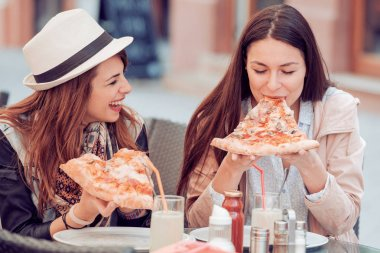 Girls eating pizza in a outdoor cafe