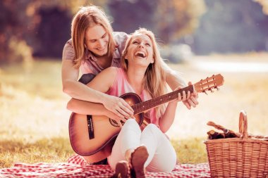 Man playing guitar to girl on a picnic