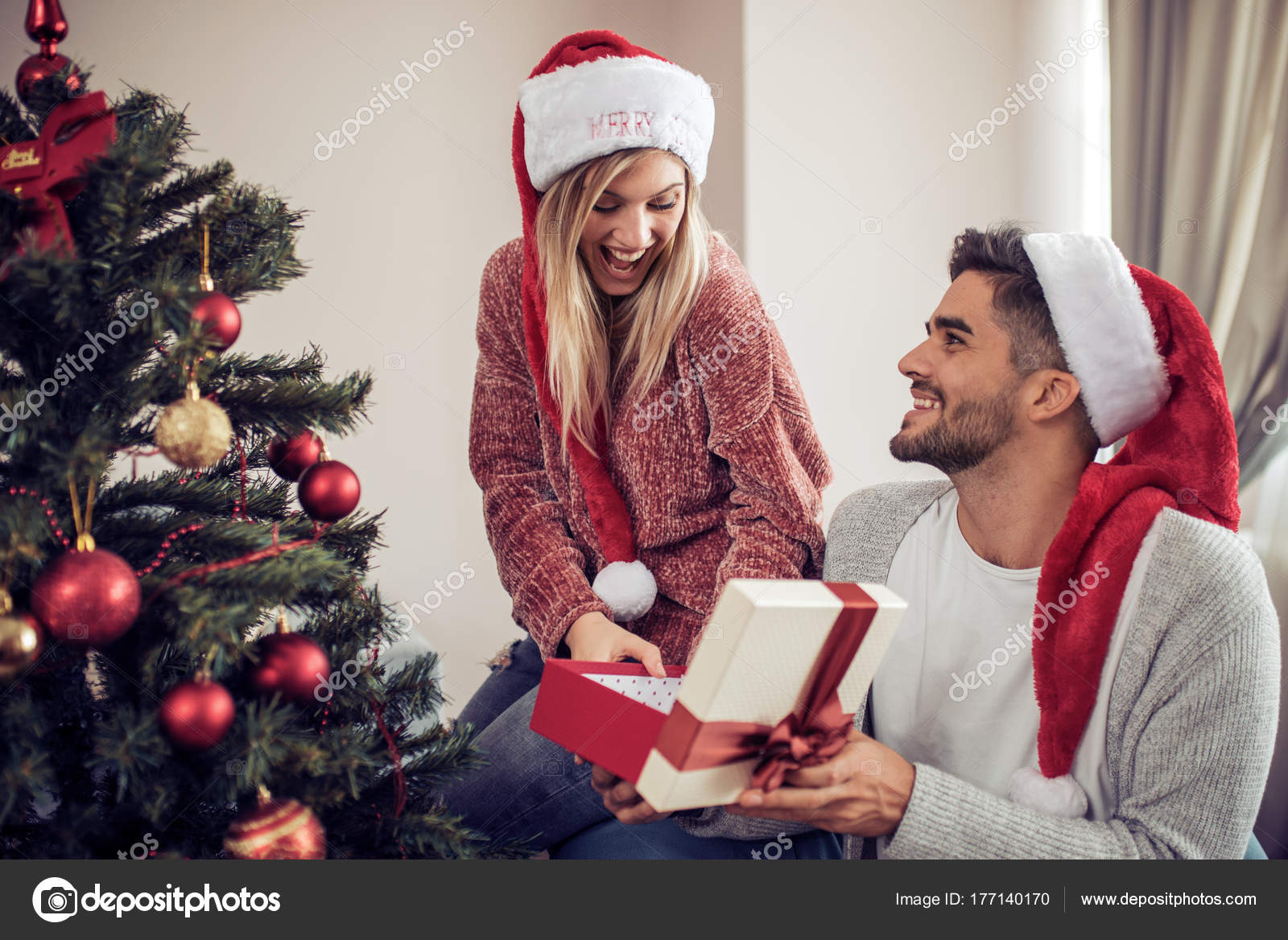 Couple exchanging gifts by Christmas tree — Stock Photo © Ivanko1980 ...