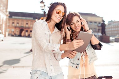 Two beautiful girls in town listening music on digital tablet.