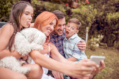 Happy family with dog taking selfie with smart phone in the park.Family, pet, technology and people concept.