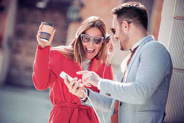 Portrait of romantic couple using mobile phone and listening to music in the street.