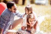 Fotografie Rodina, venkovní těší letní život dohromady. Mladá rodina v přírodě foukání pampelišky v letním dni