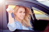 glücklich schöne junge Frau sitzt in einem Auto an einem schönen sonnigen Sommertag.