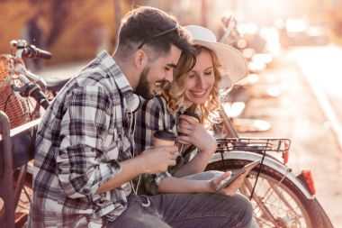 Young loving couple sitting on the park bench and having fun with tablet.Love and tenderness,lifestyle concept.