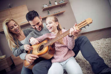 Father playing guitar for wife and daughter