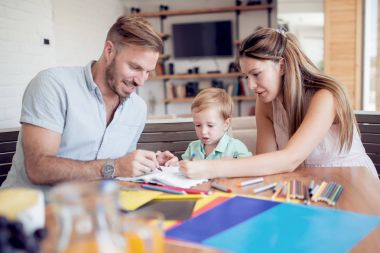 Smiling family drawing together in living room at home