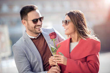 Man and woman with red rose in city