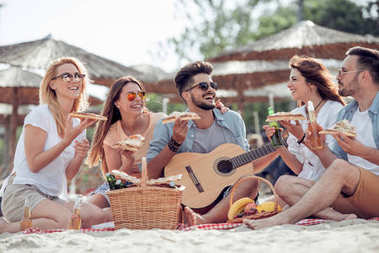 Group of friends having great time together on beach, eating pizza and playing guitar