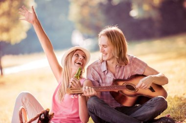 Young man playing guitar to girl on summer day in park